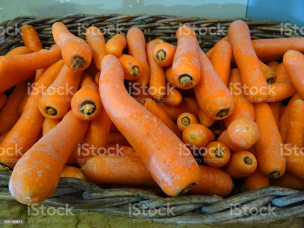 Image of fresh carrots in wicker basket at farm shop stock photo