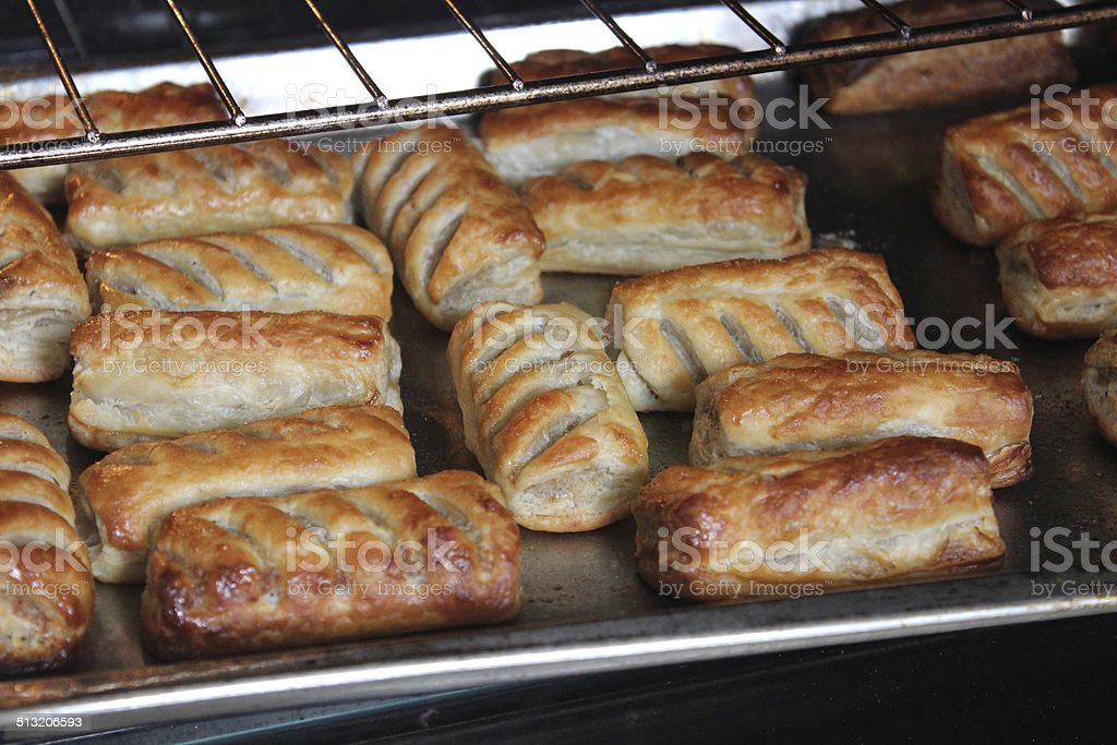 Image of freshly baked sausage rolls on oven tray, puff-pastry stock photo