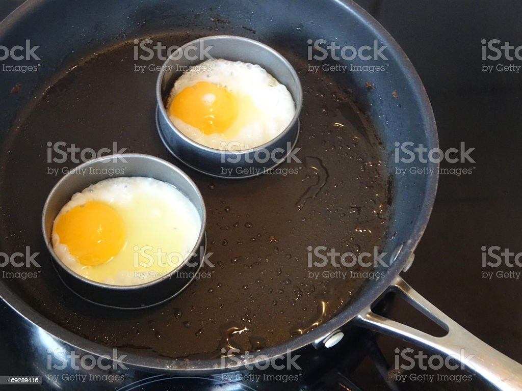 Image of fried eggs being cooking in frying-pan, non-stick rings stock photo
