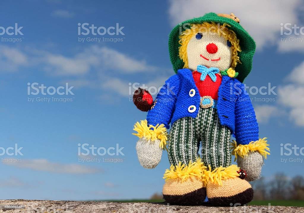 Image of friendly knitted scarecrow toy against sky background stock photo