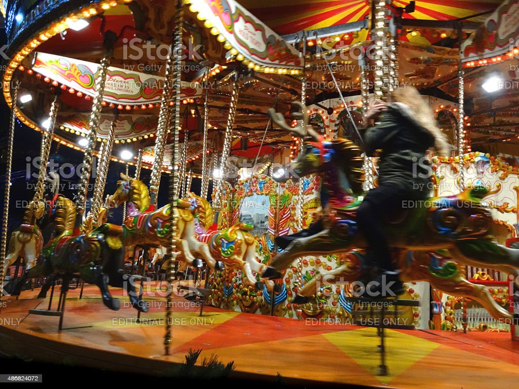 Image of funfair carousel roundabout with painted horses and light-bulbs stock photo