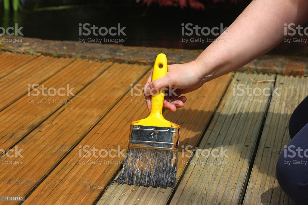 Image of garden decking being painted / stained, wood preserver varnish stock photo