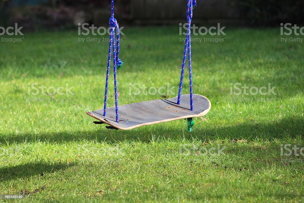 Image of garden swing made from recycled skateboard, in tree stock photo