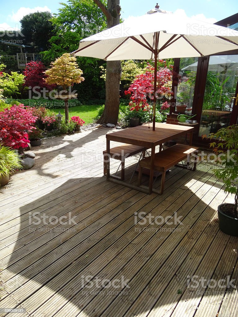 Image of garden timber-decking, table and benches with parasol umbrella stock photo
