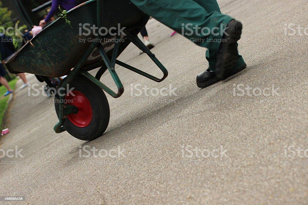 Image of gardener pushing wheelbarrow along tarmac pathway in park stock photo