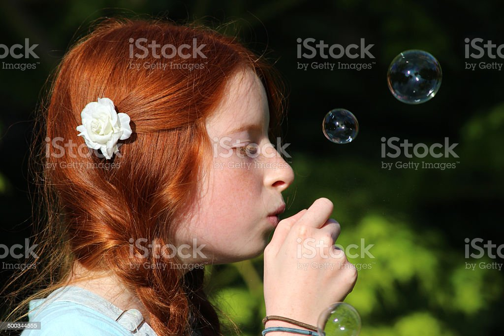 Photo showing a young girl blowing bubbles in the garden. She is...