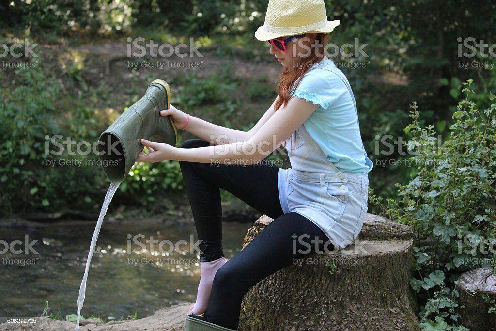 Image of girl by river, pouring water out wellie boots stock photo