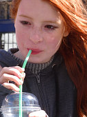 Image of girl drinking unhealthy sugary soft drink with straw