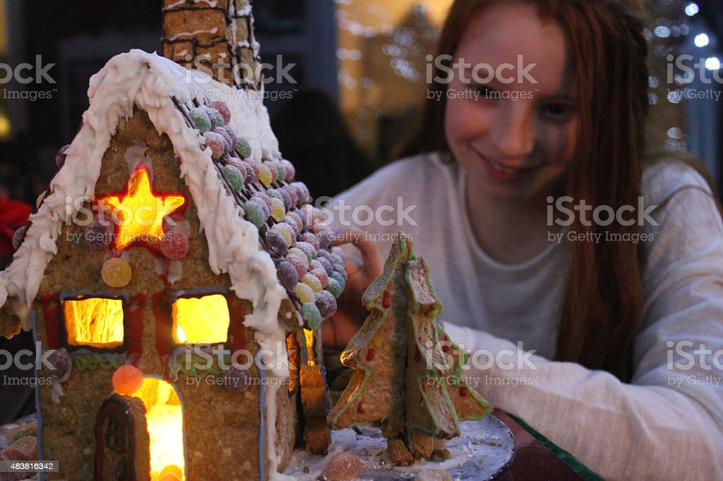 Image of girl looking at iced gingerbread house lit up stock photo