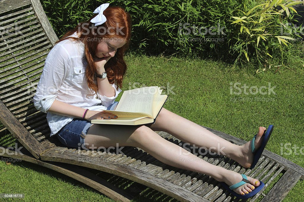Image of girl reading book in garden, wooden steamer / sunlounger stock photo