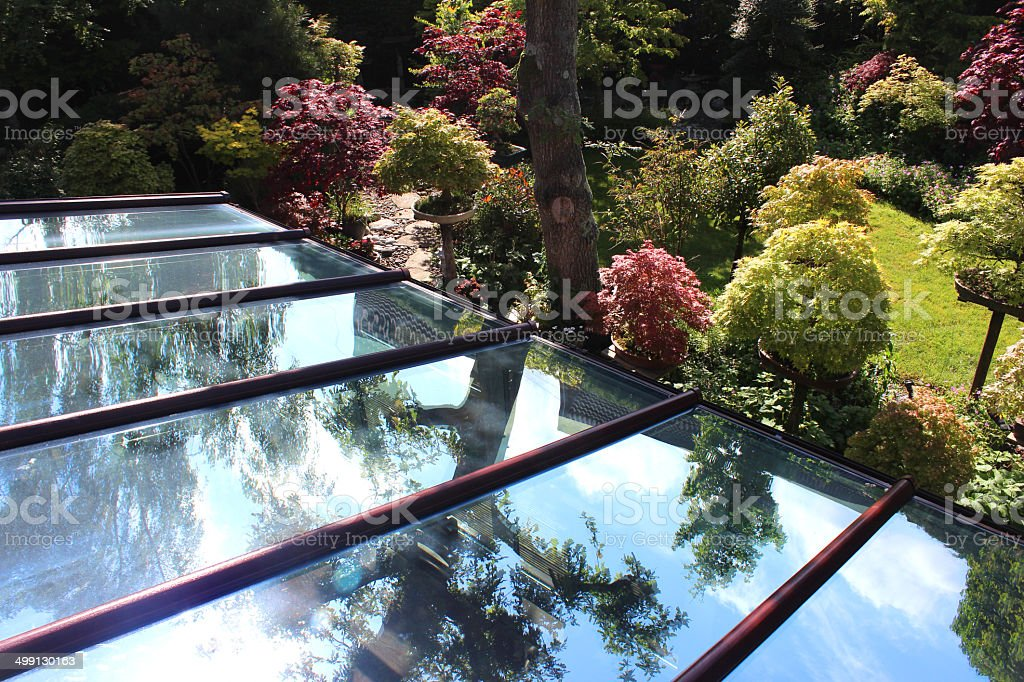 Image of glass conservatory roof panels / panes, reflecting blue sky stock photo