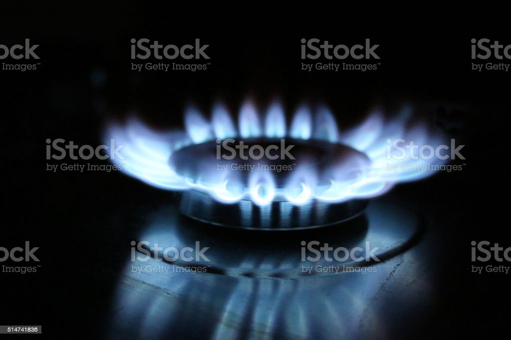 Image of glowing blue flame on burner of gas stove stock photo