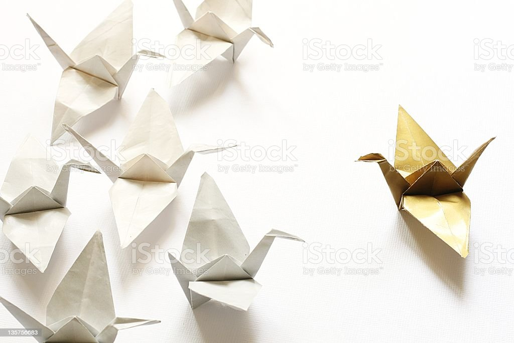 Image of gold paper crane making a speech to white ones stock photo