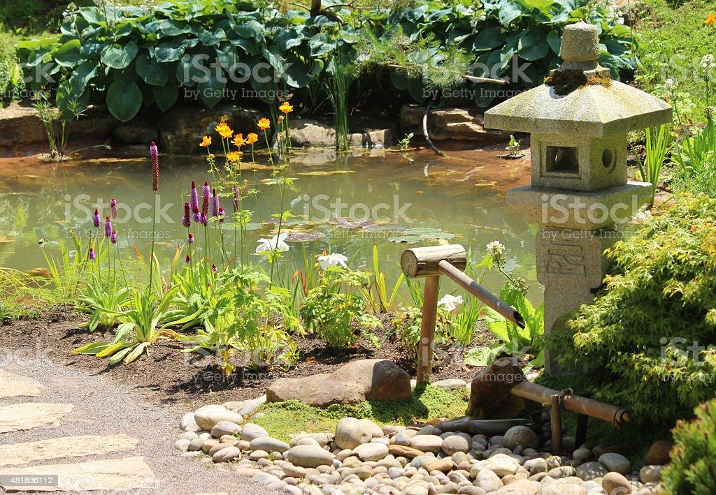 Image of granite Japanese lantern / deer scarer by garden pond stock photo
