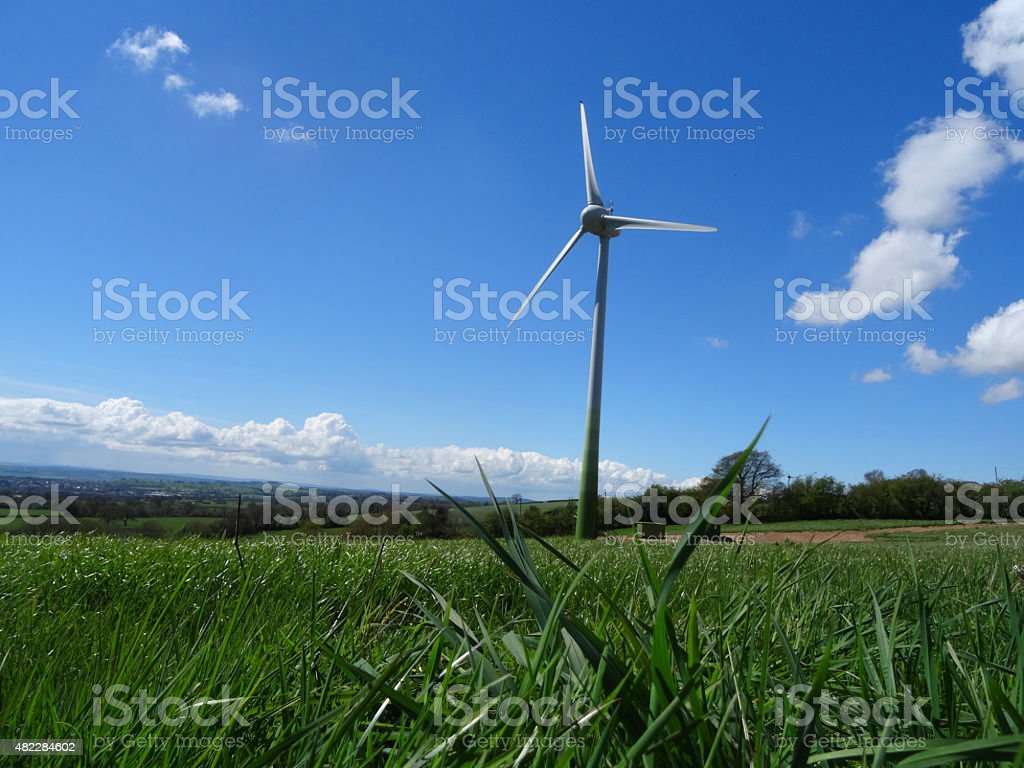 Image of grass farm field with low wind turbine windmill stock photo