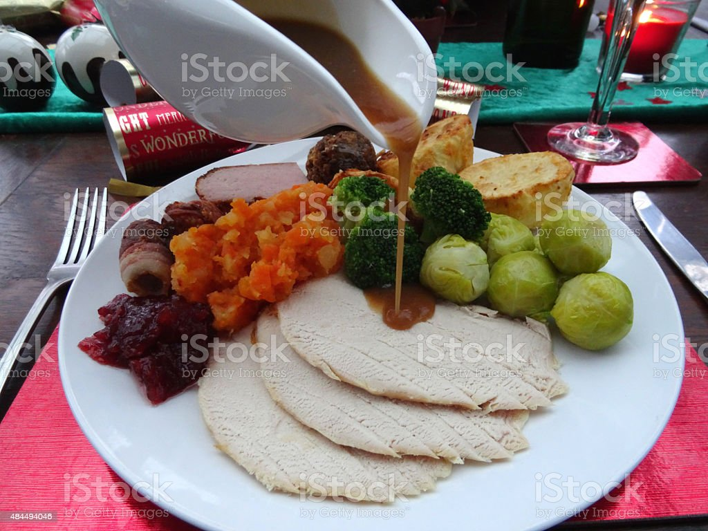 Image of gravy being poured over Christmas dinner roast turkey stock photo