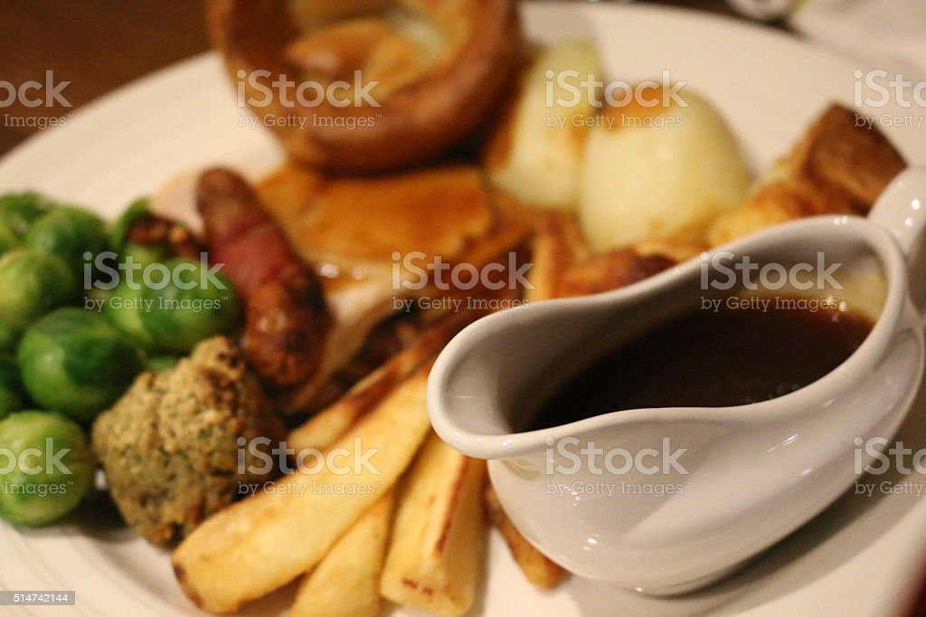 Image of gravyboat with roasted beef Sunday dinner, Yorkshire puddings stock photo
