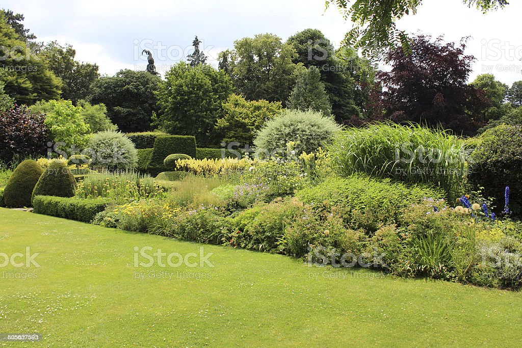 Image of green garden lawn, shrubs and herbaceous border flowers stock photo