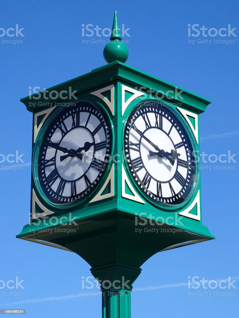 Image of green metal clock tower / clockface with Roman numerals stock photo