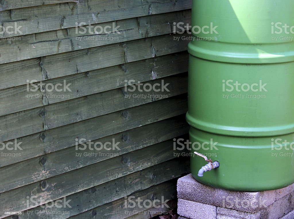 Image of green plastic water butt next to garden shed stock photo