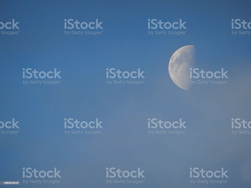 Image of half moon at end of day, against blue-sky stock photo