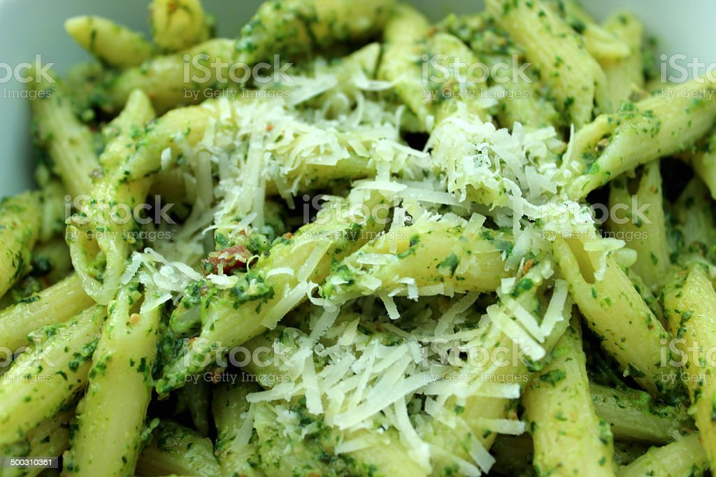 Image of homemade pesto pasta topped with grated parmesan cheese stock photo