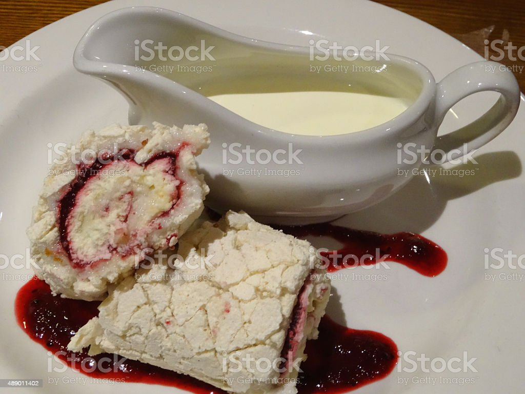 Image of homemade raspberry meringue roulade pudding with double cream stock photo
