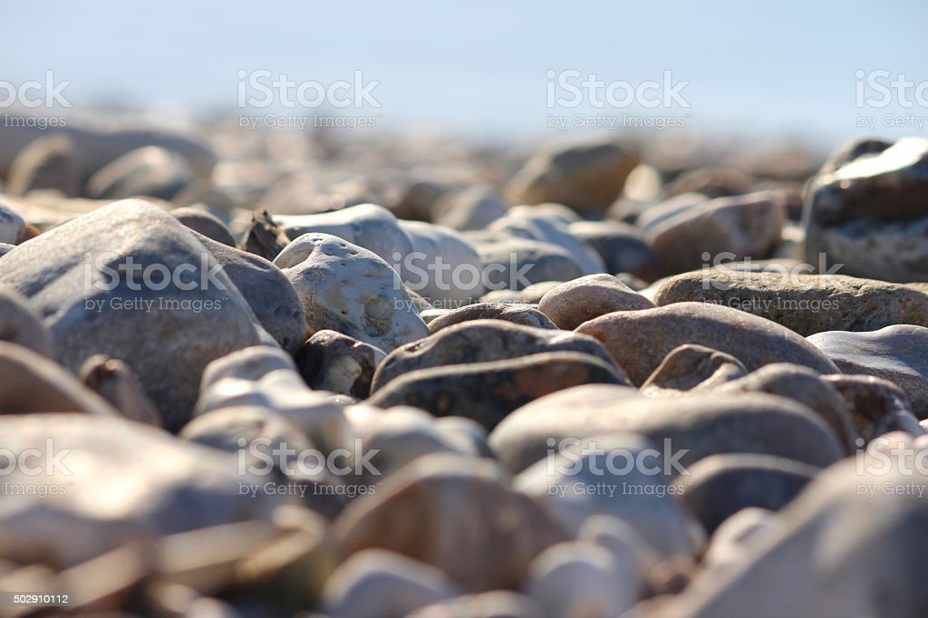 Image of irregular grey-brown beach pebbles and sand, coastal erosion stock photo