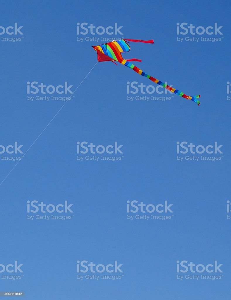 Image of kite flying in sky with rainbow stripes / long-tail stock photo