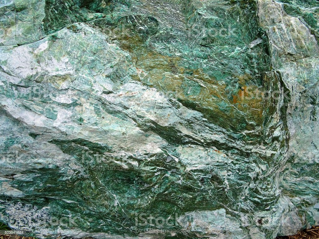 Image of large green marble rock, quartz veins, metamorphic rock-surface stock photo