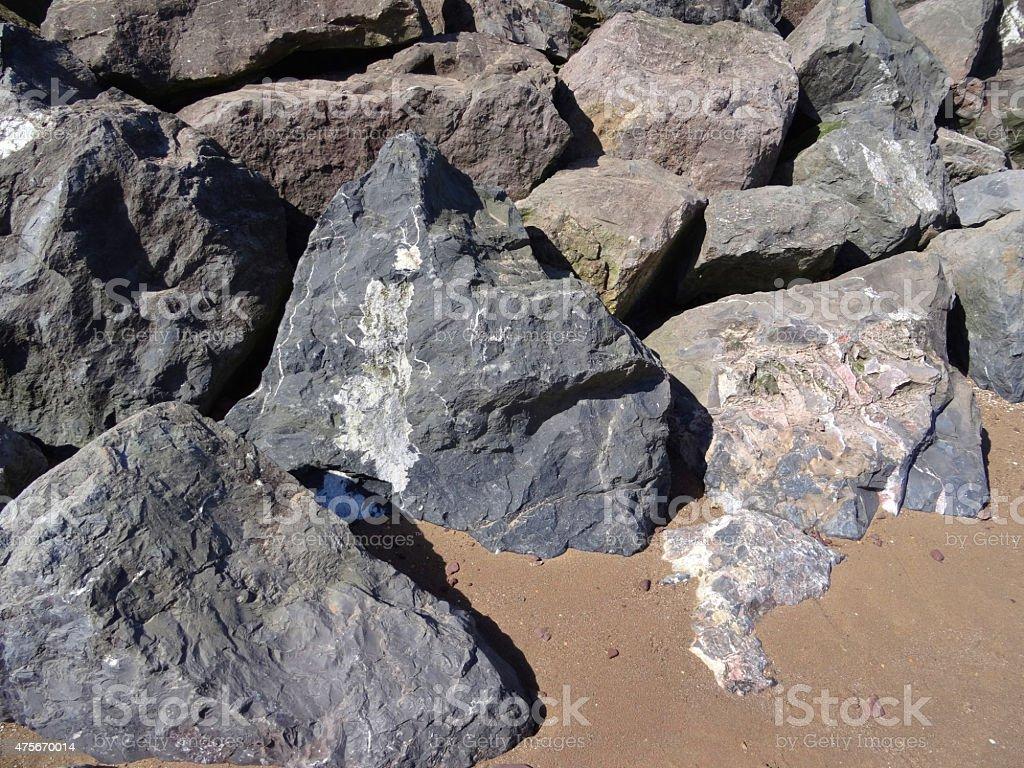 Image of large grey limestone rocks providing beach sea defence stock photo