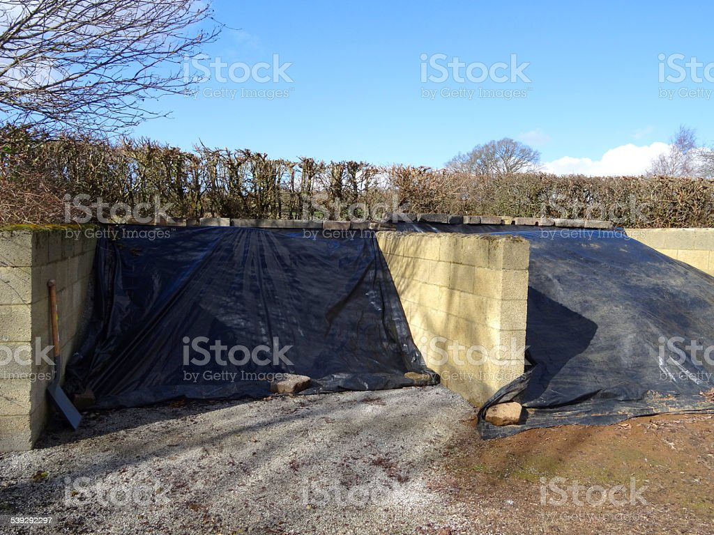 Image of large open-front compost heaps, brick walls, garden waste stock photo