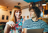 Image of lcheerful couple in cafe looking at digital tablet