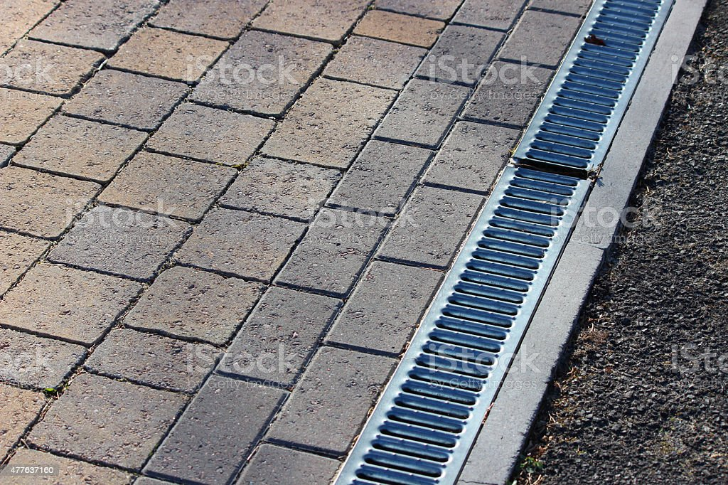 Image of linear drainage channel and grate by block-paving driveway stock photo