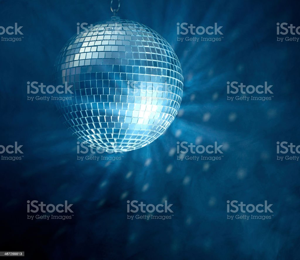 Image of lit disco ball hanging over a darkened dance floor stock photo