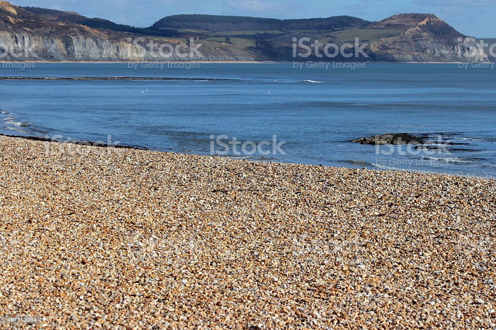 Image of Lyme Regis pebble beach, sea, cliffs and sky stock photo