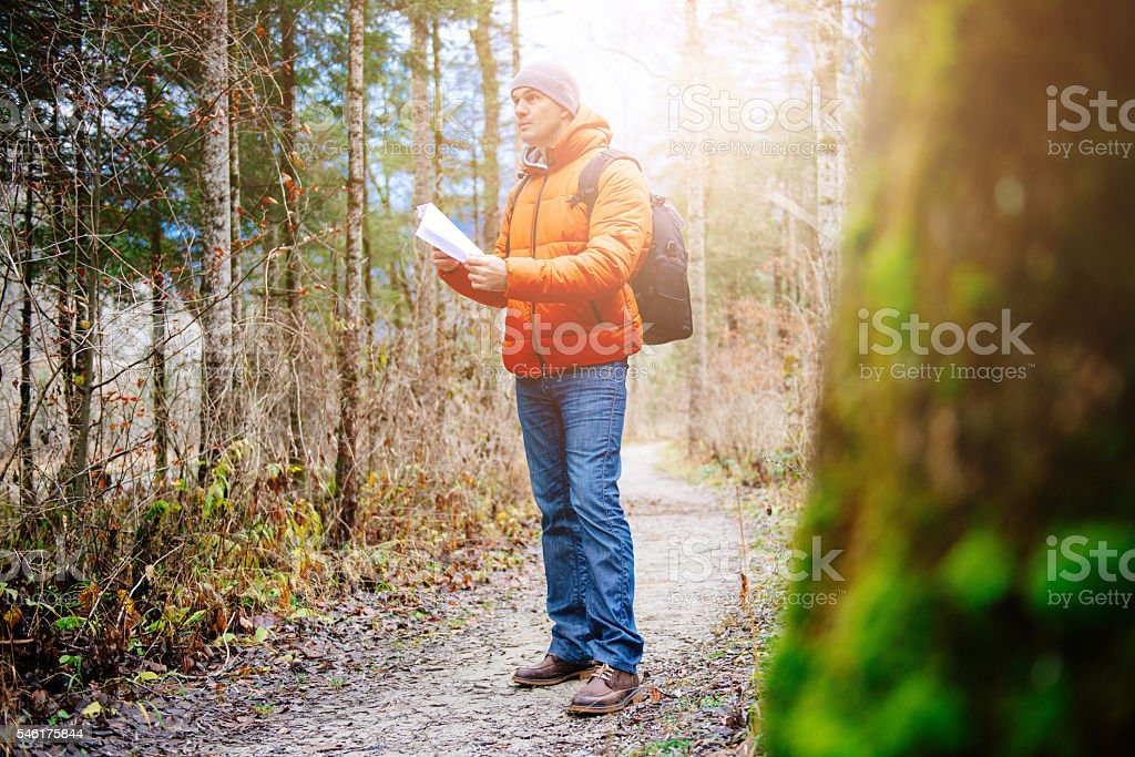Image of man hiking and orienteering in woods in winter stock photo