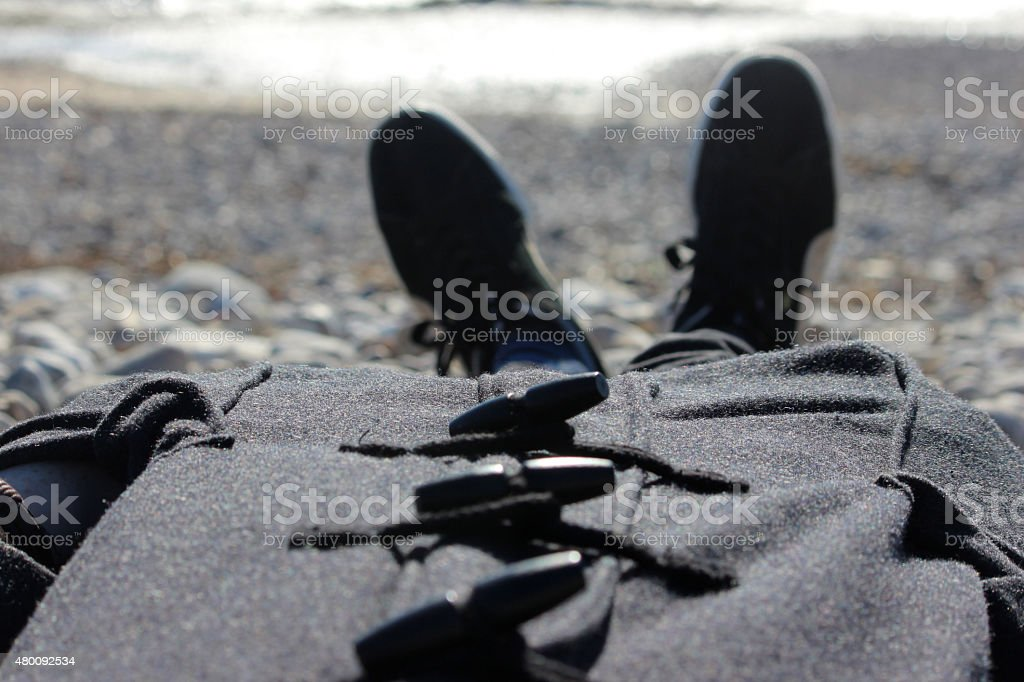 Image of man sunbathing in the winter, wearing duffle coat stock photo