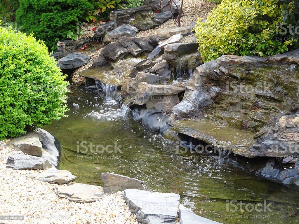 Image of manmade fibreglass waterfalls with realistic grey plastic rocks stock photo