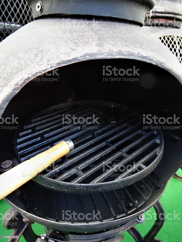 Image of metal chiminea / chimenea outdoor fireplace with barbecue grill stock photo