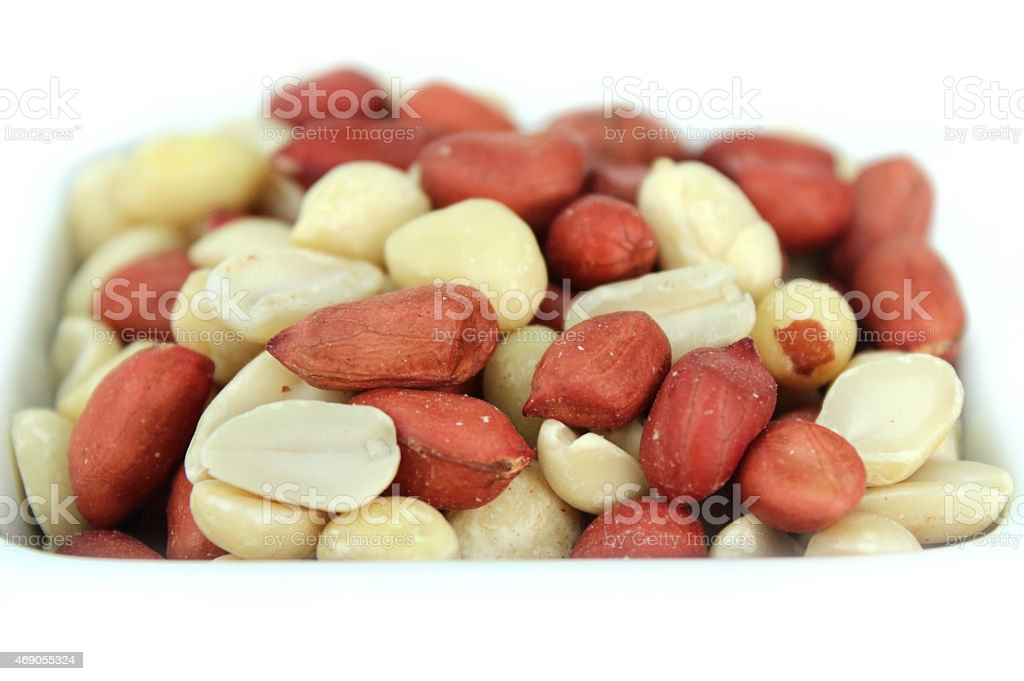Image of mixed red-skin peanuts in white dish, healthy snack stock photo