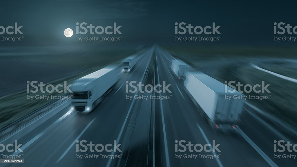 Image of modern delivery trucks on the highway at night stock photo