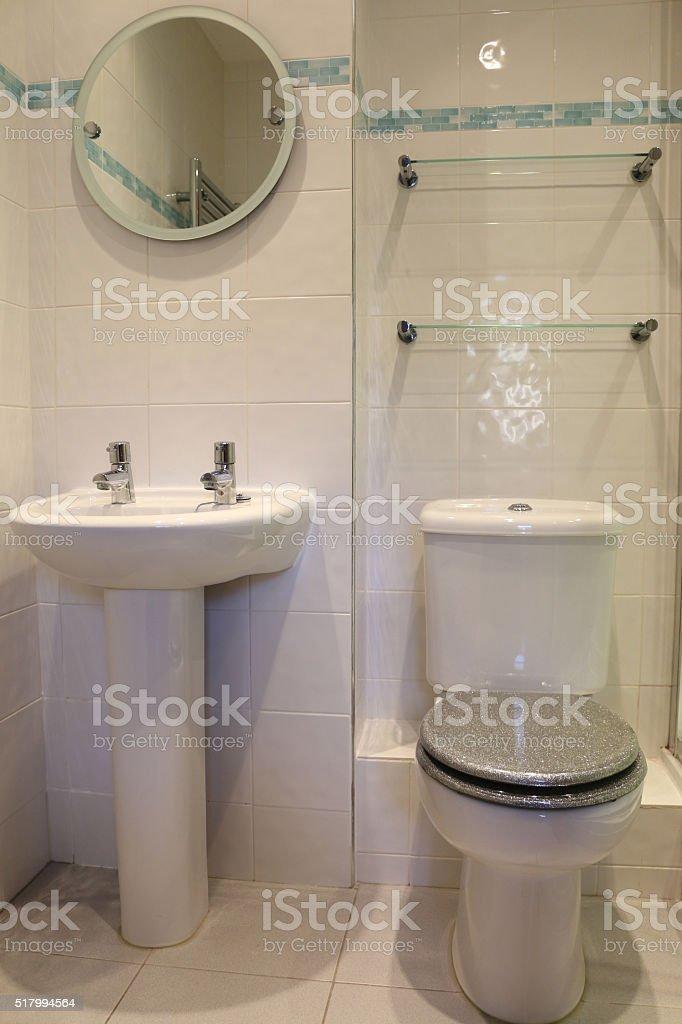 Image of modern, white tiled bathroom, pedestal wash-basin / sink, toilet stock photo