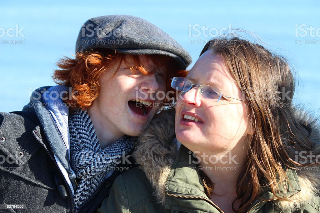 Image of mother and teenage son laughing together at beach stock photo