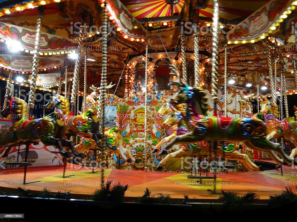 Image of moving carousel roundabout with lights, painted / decorated horses stock photo