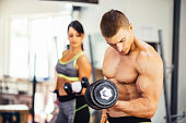 Image of muscular couple exercising weightlifting in gym