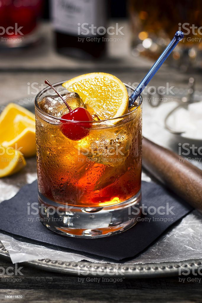 Image of old fashioned cocktail with fruits on black napkin stock photo