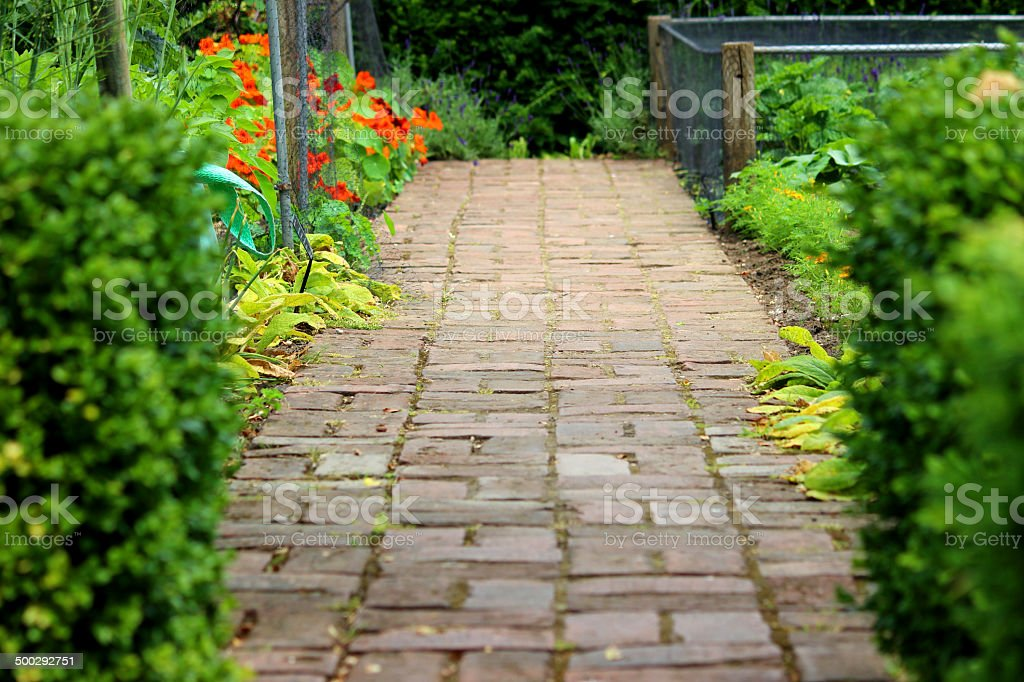 Image of old red brick pathway, formal ornamental vegetable garden stock photo