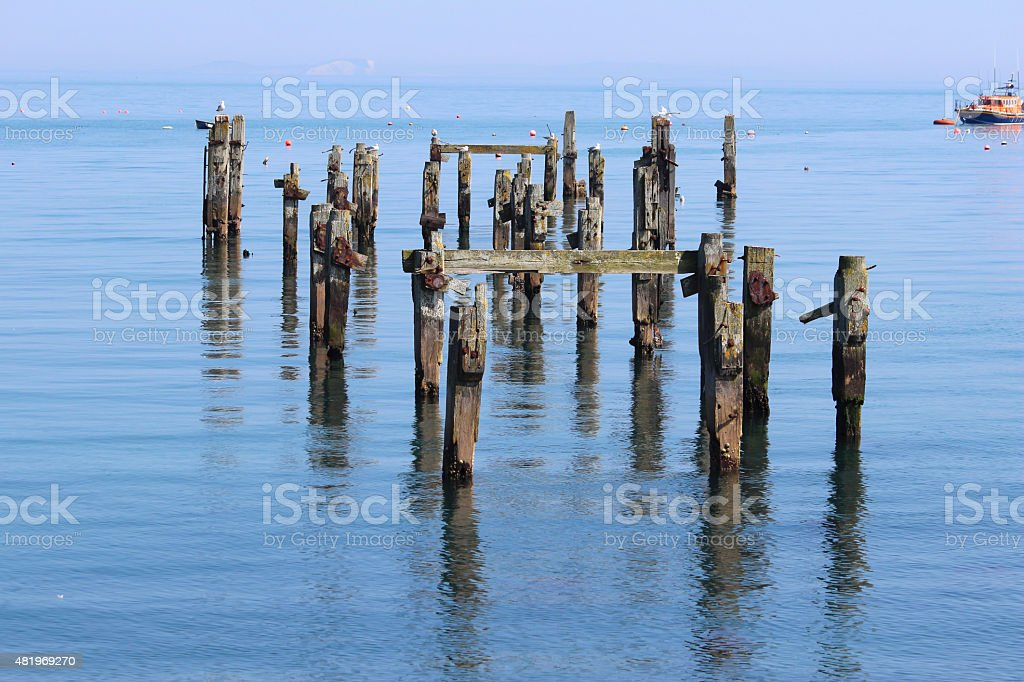 Image of old Swanage pier with rotten wooden posts / lifeboat stock photo