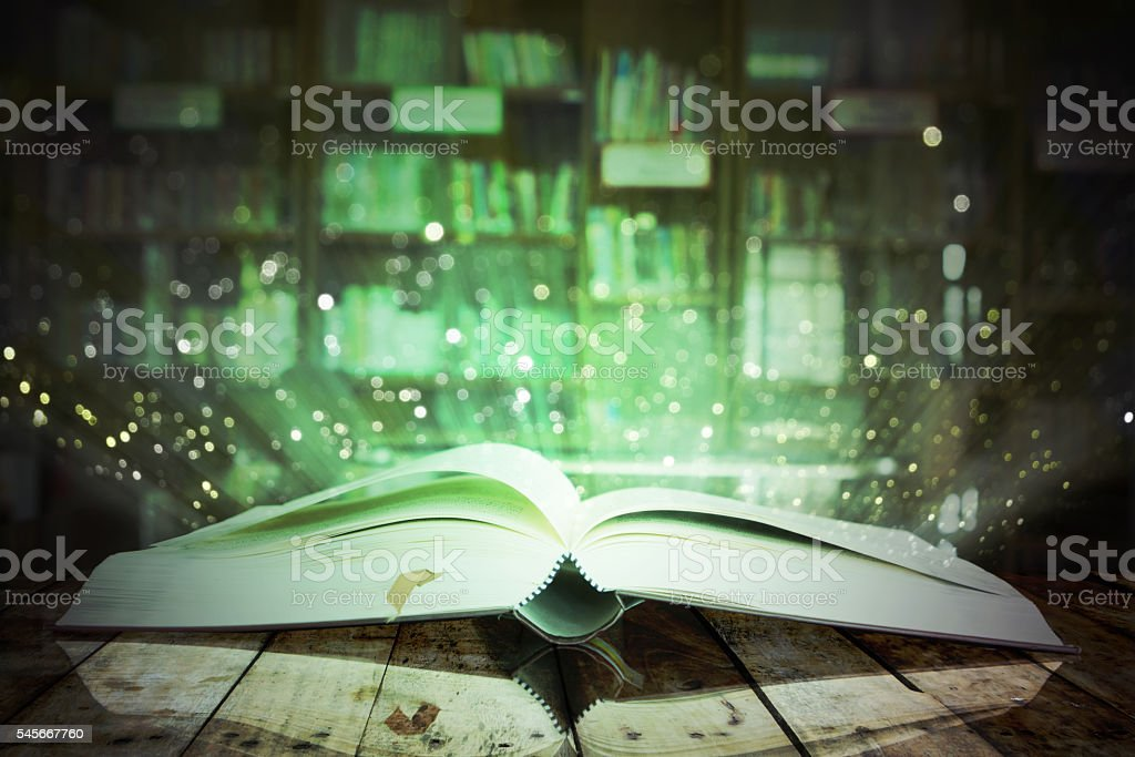 Image of opened magic book with glister lights. stock photo